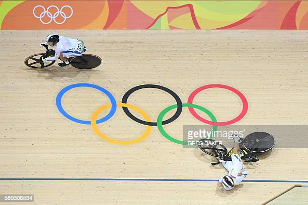 South Korea's Lee Hyejin rides past as Colombia's Martha Bayona Pineda falls during the women's Keirin second round track cycling event at the...