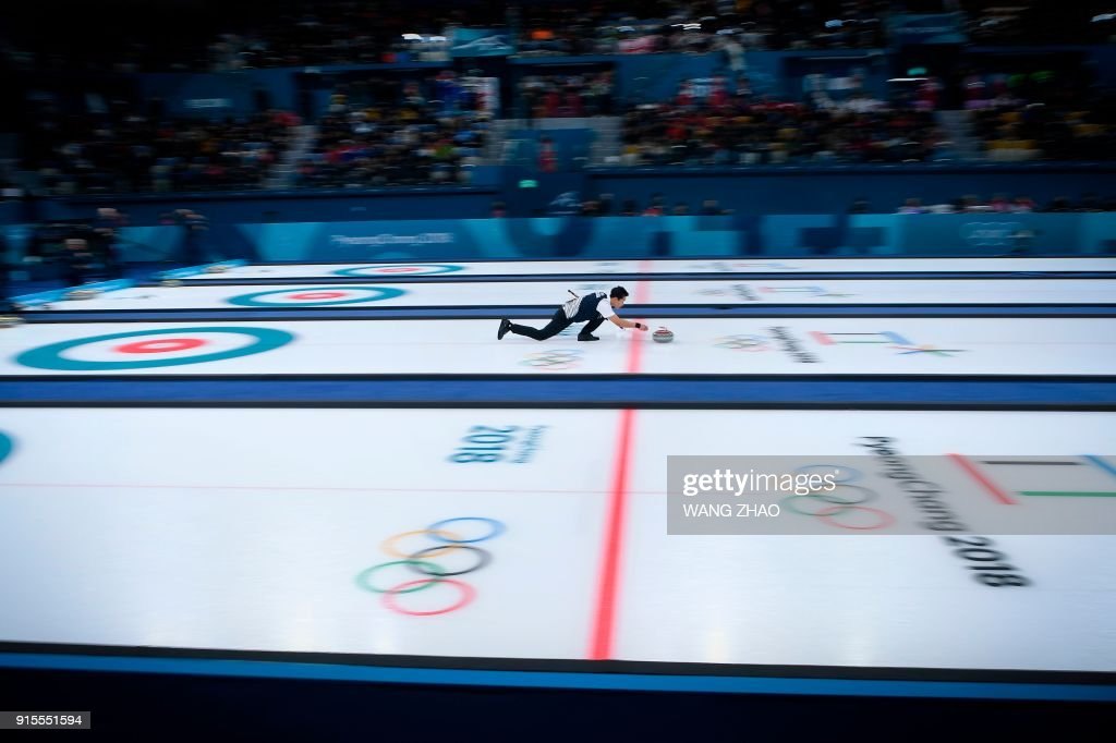 TOPSHOT - South Korea's Lee Kijeong throws the stone during the curling mixed doubles round robin session between South Korea and Finland during the Pyeongchang 2018 Winter Olympic Games at the Gangneung Curling Centre in Gangneung on February 8, 2018. / AFP PHOTO / WANG Zhao
