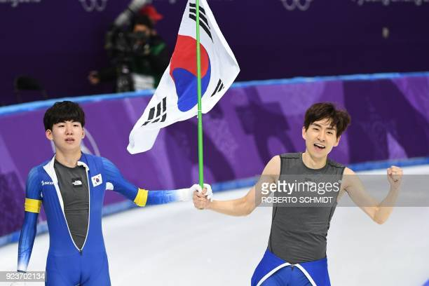 South Korea's Lee Seung-Hoon celebrates his gold medal win alongside compatriot Chung Jaewon, who finished eighth, in the men's mass start final...
