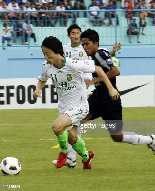 South Korea's Lee Sung Hyun from Jeonbuk Hyundai Motors vies for the ball against Indonesia's Ahmad Amiruddin of Arema Indonesia during the group G...