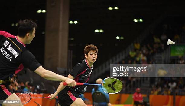 South Korea's Lee Yong Dae and South Korea's Yoo Yeon Seong return during their men's doubles qualifying badminton match against Russia's Vladimir...