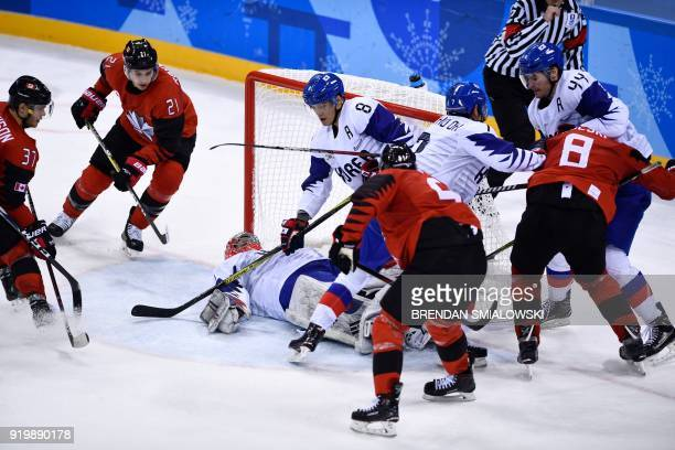 South Korea's Matt Dalton lies on the ice as players scuffle in the men's preliminary round ice hockey match between Canada and South Korea during...