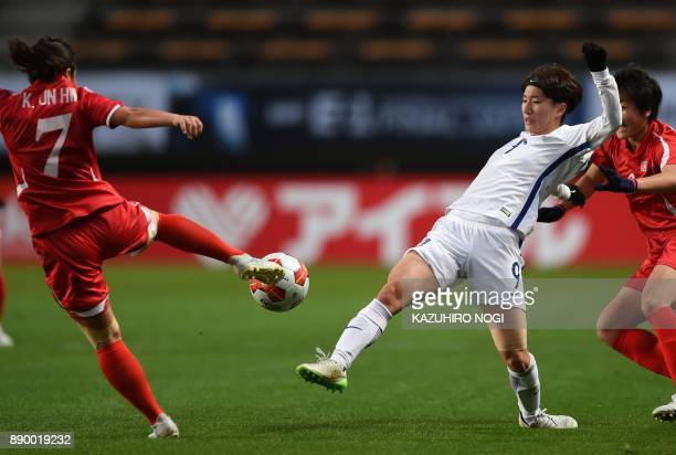South Korea's midfielder Kang Yumi and North Korea's midfielder Kim Un Hwa fight for the ball during the women's football match between North Korea...