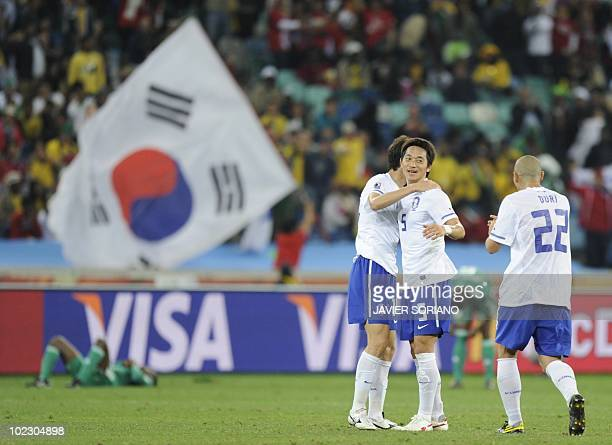 South Korea's midfielder Kim NamIl and South Korea's defender Cha DuRi celebrate their victory with other players at the end of the Group B first...