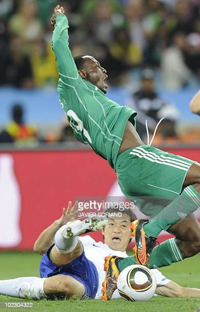 South Korea's midfielder Kim NamIl falls as Nigeria's striker Chinedu Obasi jumps during their Group B first round 2010 World Cup football match on...