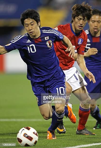 South Korea's midfielder Lee Chung-Yong challenges Japan's forward Shinji Kagawa during their 2011 Asian Cup semi-final football match at Al-Gharafa...