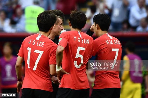 South Korea's midfielder Lee Jaesung South Korea's defender Yun Youngsun and South Korea's forward Son Heungmin argue with US referee Mark Geiger on...