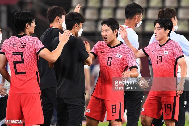 South Korea's midfielder Lee Kang-in celebrates with teammates after South Korea won the Tokyo 2020 Olympic Games men's group B first round football...