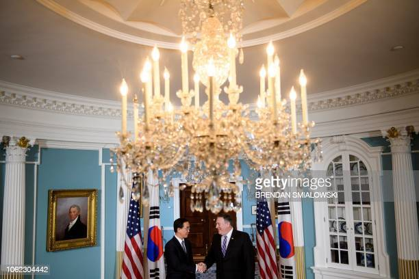 South Korea's Minister of Unification Cho Myounggyon and US Secretary of State Mike Pompeo shake hands before a meeting at the US Department of State...