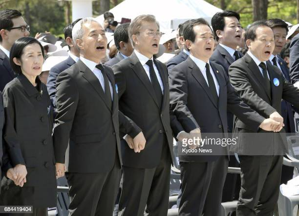 South Korea's new President Moon Jae In holds hands with attendees and sings a song at a ceremony marking the 37th anniversary of a 1980 prodemocracy...