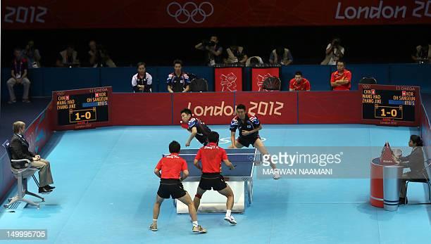 South Korea's Oh Sangeun and South Korea's Ryu Seungmin return a ball to China's Wang Hao and Zhang Jike during the table tennis men's team final...