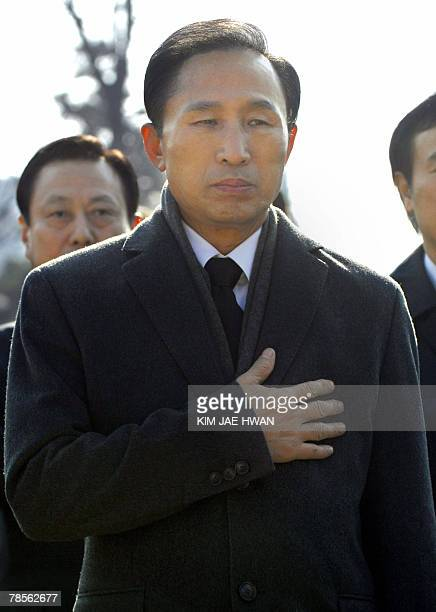 South Korea's opposition Grand National Party presidential candidate Lee MyungBak puts his hand over his heart to give a salute for the 75th death...