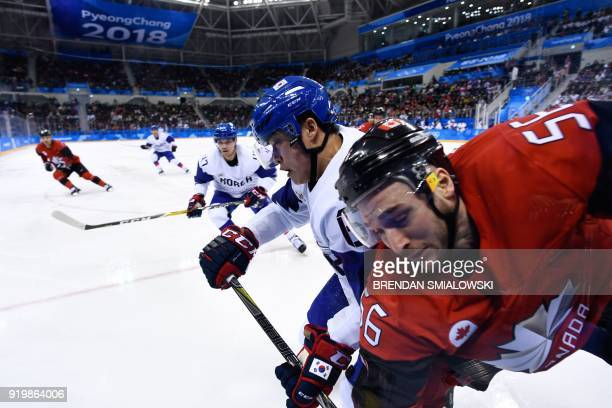 South Korea's Park Jin Kyu checks Canada's Maxim Noreau in the men's preliminary round ice hockey match between Canada and South Korea during the...