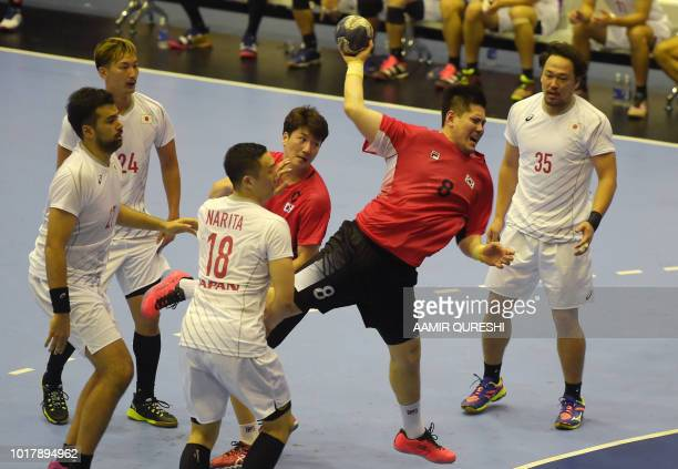 South Korea's Park Junggeu attempts a goal as Japan's players look on during the men's handball preliminary group B match between South Korea and...