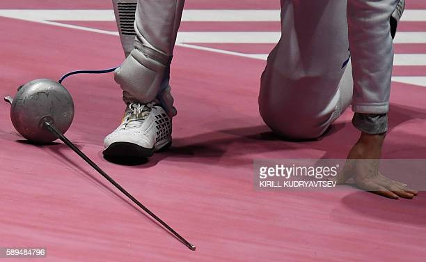 South Korea's Park Sangyoung touches his ankle during the mens team epee classification 58 bout between Venezuela and South Korea as part of the...