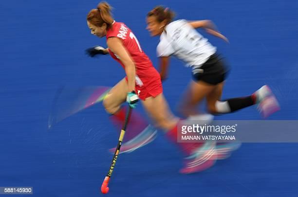South Korea's Park Seunga and Germany's Selin Oruz chase the ball during the women's field hockey Germany vs South Korea match of the Rio 2016...