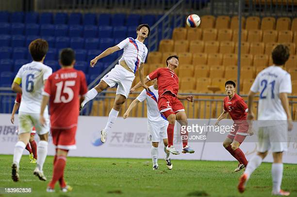 South Korea's Park Song Il jumps for the ball with North Korea's Kim Jung Joo during their football match at the East Asian Games in Tianjin on...