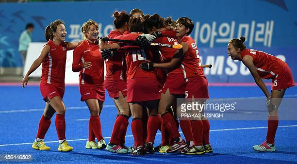 South Korea's players celebrate their win over China during their women's field hockey gold medal match at the Seonhak Hockey Stadium during the 17th...