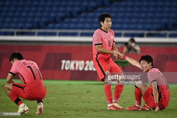 South Korea's players react react to their loss in the Tokyo 2020 Olympic Games men's quarter-final football match between Republic of Korea and...