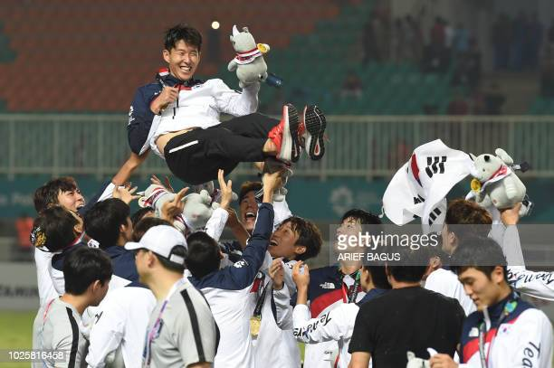 South Korea's players toss their teammate Son Heungmin in the air after the victory ceremony for the mens football competition at the 2018 Asian...