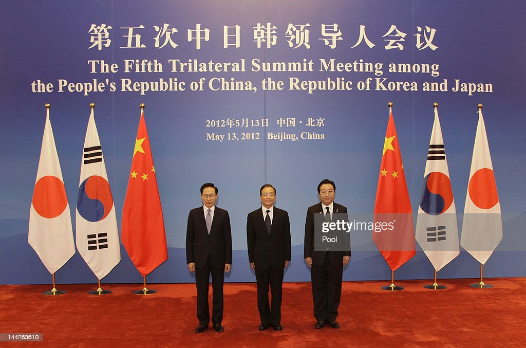 South Korea's President Lee Myung-bak, China Premier Wen Jiabao and Japanese Prime Minister Yoshihiko Noda pose in front of their national flags at the Great Hall of the People May 13, 2012 in Beijing, China. The three are meeting for talks focused on maintaining strong relations, the global economy and disaster relief. The trilateral summits began in 2008.