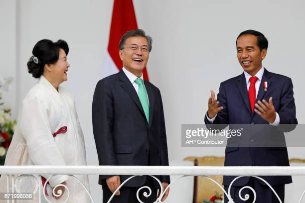 South Korea's President Moon Jae-in and his wife Kim Jung-sook listen to Indonesia's President Joko Widodo on the balcony of the presidential palace...