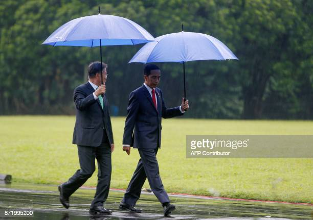 South Korea's President Moon Jae-in and Indonesia's President Joko Widodo hold umbrellas as they walk to a tree planting session at the Presidential...