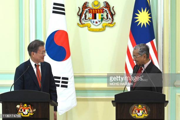 South Korea's President Moon Jae-in and Malaysia's Prime Minister Mahathir Mohamad look at each other during a joint press conference in Putrajaya on...