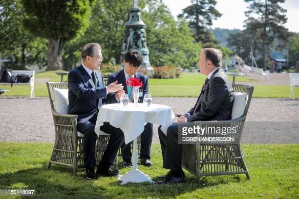 South Korea's President Moon Jae-in and Sweden's Prime Minister Stefan Lofven talk in the garden at Grand Hotel in Saltsjobaden outside Stockholm, on...