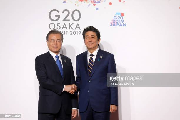 South Korea's President Moon Jaein is welcomed by Japan's Prime Minister Shinzo Abe to the G20 Summit in Osaka on June 28 2019