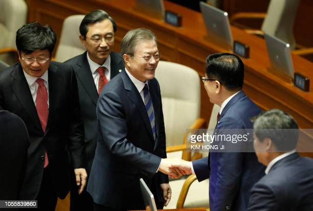 South Korea's President Moon Jaein shakes hands as he leaves after delivering a speech on the government's 2019 budget proposal during a plenary...