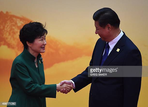 South Korea's President Park GeunHye shakes hands with China's President Xi Jinping as she arrives for the AsiaPacific Economic Cooperation leaders...