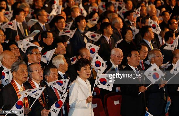 South Korea's President Park Geun-hye waves a national flag during a ceremony celebrating the 95th anniversary of the March First Independence...