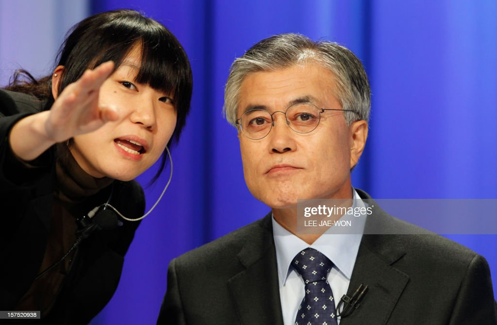 South Korea's presidential candidate Moon Jae-In (R) of the main opposition Democratic United Party talks with a staff member of a TV station before a televised debate in Seoul on December 4, 2012. Conservative and right wing Park who is the daughter of late South Korean military dictator Park Chung-hee and the former human rights lawyer Moon, participated in a debate over security policy as North Korea readied a rocket launch that is timed to coincide with the South's presidential election.