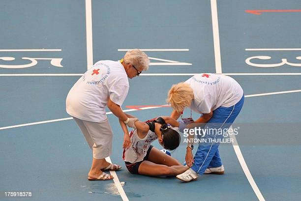 South Korea's Seongeun Kim is helped after collapsing following the woman's marathon final at the 2013 IAAF World Championships at the Luzhniki...