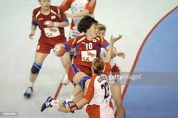 South Korea's Seongok Oh tries to score despite Hungary's Gabriella Szucs during the women world championship handball match Hungary vs South Korea...