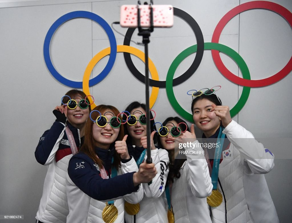TOPSHOT - South Korea's short track gold medallists Shim Sukhee, Choi Minjeong, Kim Yejin, Kim Alang and Lee Yubin pose for a selfie with their medals in front of Olympic rings backstage at the Athletes' Lounge during the medal ceremonies at the Pyeongchang Medals Plaza during the Pyeongchang 2018 Winter Olympic Games in Pyeongchang on February 21, 2018. /