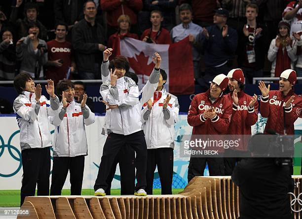 South Korea's silver medallists celebrate on the podium with Canada's gold medallists during the medal ceremony at the end of the Men's 5000 m relay...