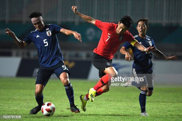South Korea's Son Heung Min fights for the ball with Japan's Daiki Sugioka in the men's gold medal football match at the 2018 Asian Games in Bogor on...