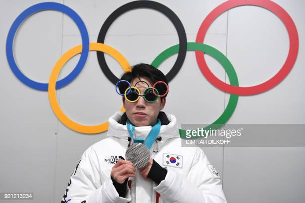 South Korea's speed skating silver medallist Cha Min Kyu poses in front of Olympic rings backstage at the Athletes' Lounge during the medal...