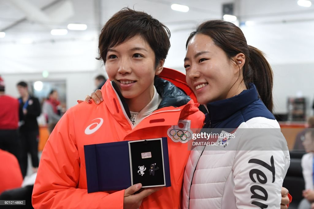 South Korea's speed skating silver medallist Lee Sang-Hwa (R) and Japan's speed skating gold medallist Nao Kodaira pose together backstage at the Athletes' Lounge during the medal ceremonies at the Pyeongchang Medals Plaza during the Pyeongchang 2018 Winter Olympic Games in Pyeongchang on February 20, 2018. / AFP PHOTO / Dimitar DILKOFF