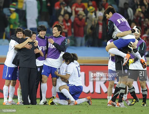 South Korea's striker Park ChuYoung and midfielder Kim JaeSung embrace as teammates celebrate their victory at the end of the Group B first round...
