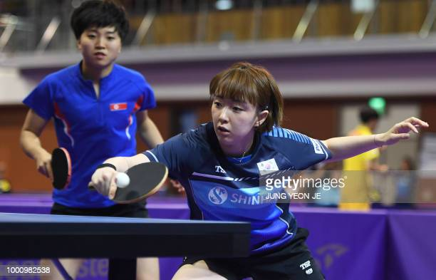 South Korea's Suh Hyowon returns the ball as teammate North Korea's Kim Song I looks on against Uzbekistan's Olga Kim and Regina Kim during the...