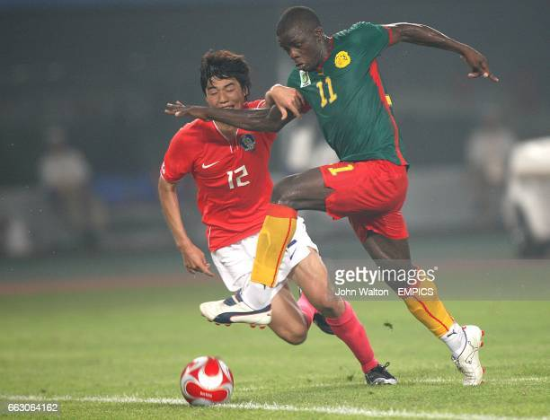 South Korea's Sung Yeung Ki and Cameroon's Gustave Bebbe battle for the ball