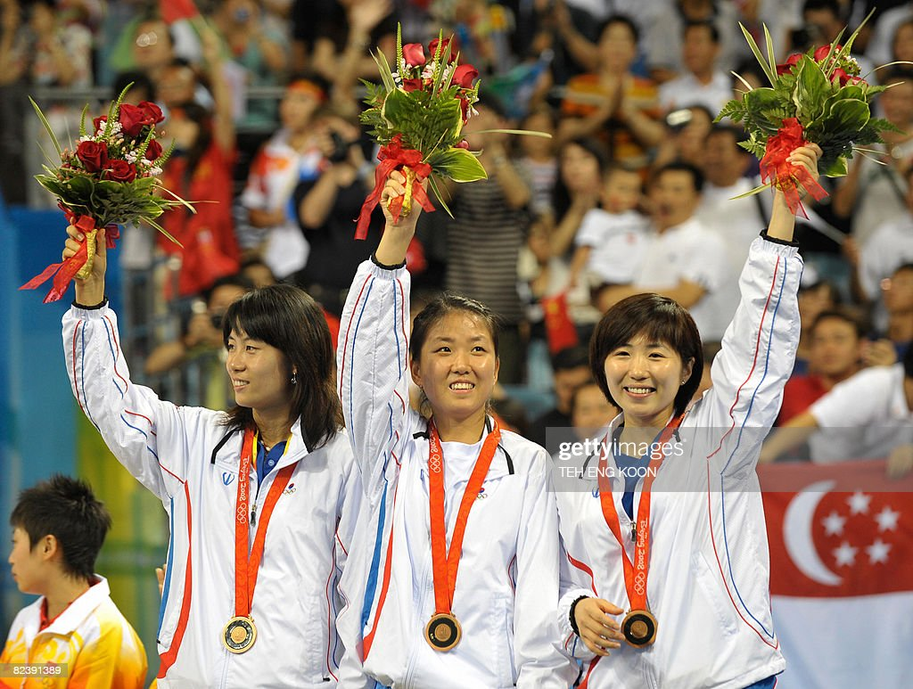 South Korea's table tennis team Dang Ye Seo (L), Pang Mi Young (C) and Kim Kyung Ah (R) wave to spectators after they won the Bronze medal in the women's team table tennis of the 2008 Beijing Olympic Games at the Peking University gymnasium in Beijing on August 17, 2008. AFP PHOTO/TEH Eng Koon