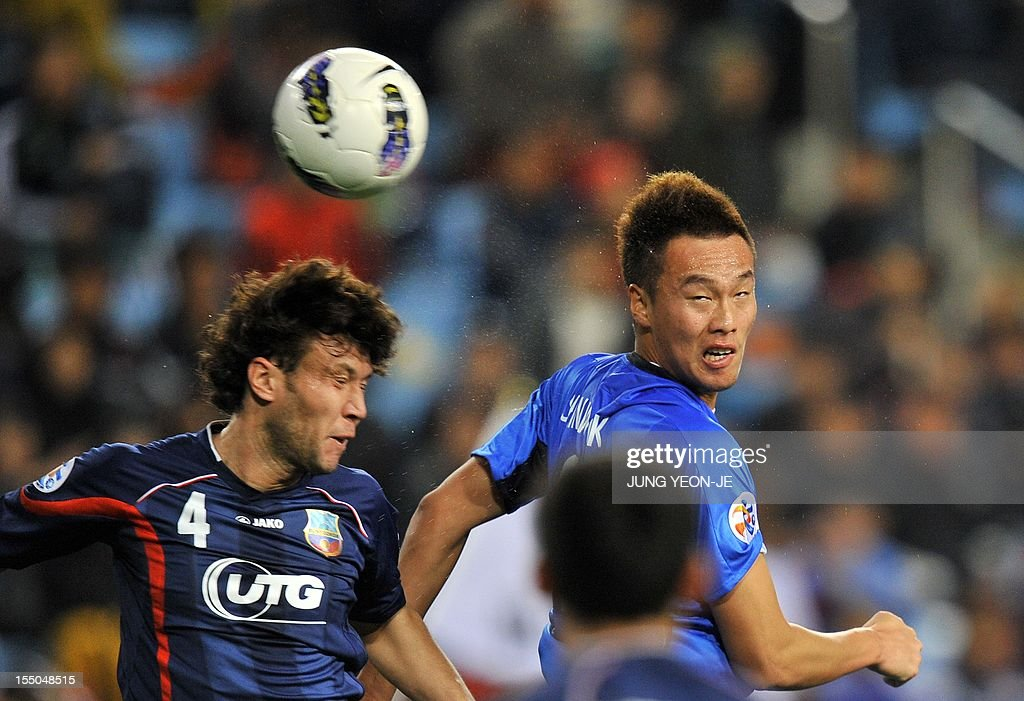 South Korea's Ulsan Hyundai forward Kim Shin-Wook (R) jumps for the ball with Uzbekistan's Bunyodkor defender Karimov Hayrulla (L) during the AFC Champions League semi final match in Ulsan, about 3...