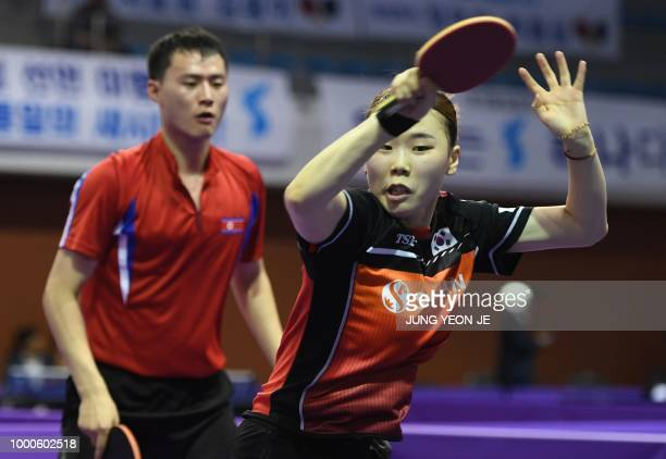 South Korea's Yoo Eunchong returns the ball as her partner North Korea's Choe Il looks on during their preliminary round match against Spain's Alvaro...