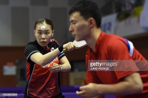 South Korea's Yoo Eunchong serves the ball as her partner North Korea's Choe Il looks on during their preliminary round match against Spain's Alvaro...