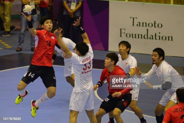 South Korea's Yoon Ciyoel passes the ball as Japan's players look on during the men's handball preliminary Group B match between South Korea and...