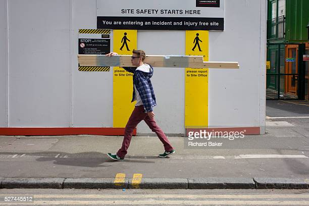 South London youth carries timber over his shoulder past the site entrance of the regeneration project at Elephant Castle London borough of Southwark...